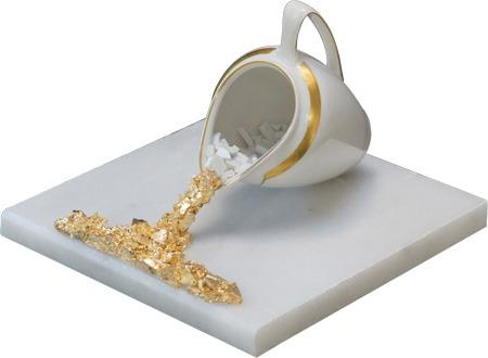 Milchkännchen mit Gold-Milch auf Marmorplatte
